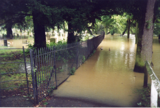 In AUgust 2001 after a day of record rainfall the river burst its banks and flooded part of the churchyard, as well as much of the rest of the centre of the village. This picture was taken from Fleming's Bridge looking along the riverbank path. | Neil Fortey, August 2001