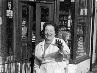 Moulsher's village store on Market St, Bottesford. Mrs Moulsher is in the foreground, and rearing through the window of the store is Mrs Jean Dunsmore.   Contributed by Mrs Anne Moulsher