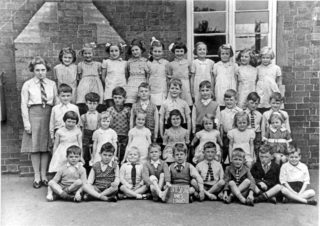 Bottesford Infants Class, 1940 - Teacher: Miss Morris (Mrs Edinburgh).  Back row (left to right): not identified, Sheila Coy, Pat Robinson, Ann Lovett, Paddy Jameson, Vera Skinner, Jean Bend, Daphne Marsden, Eileen Fenton, Kathleen Doubleday;  Third row (left to right): Francis Stubley, Herbert Turner, John Skinner, Richard Pacey, Keith Samuel, Brian Branston, Jeff Boland, George Pearson, Ian Norris;  Second row (left to right): Pat Taylor, Beryl Lamb, Dot Bend, Margaret Deacon, Sheila Mumby, Gina Topps, Gillian Isaac;  Front row (left to right): Maurice Fisher, Gerald Pacey, Peter Holmes, Richard Higdon, Peter Stanley, Gel Dolby, Peter Abbott, not identified, Peter Olley. | Bottesford Local History Archive - contributed by Mrs Wendy Cross