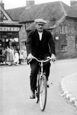 Mr Slater cycling past Standley's store
