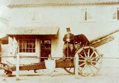 Gentleman sitting on german gun outside Taylor's shop