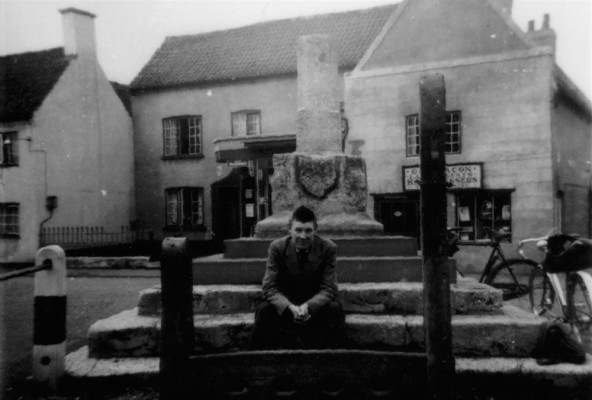 Cyclist resting on steps of Bottesford market cross