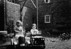 Richard and Robert Bond in pedal cars in Six Bells yard