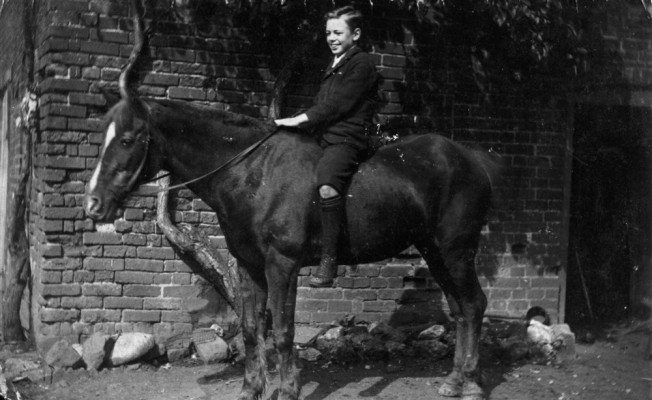 Tom Samuel seated on pony in yard