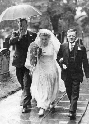 Wedding picture, Betty Robinson being given away by her father Tommy Robinson, walking along the path to the porch of St Mary's. | Bottesford Heritage Archive