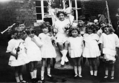 infant girls with May Queen in school yard