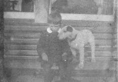 A poor picture of a boy sitting on a bench with his pet terrier