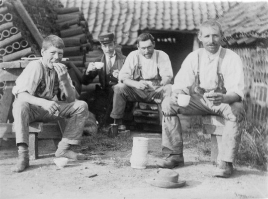 Four men enjoying a break during their work at Challand's brickyard, Normanton Lane, Bottesford. The man at the back of the group is wearing railway uniform and may be a brother of the old of the brick makers. The lad is probably a son. | Contributed by Mrs Jean Round