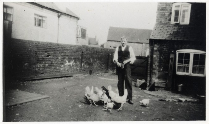 Reg Barke with chickens in yard at Bottesford Coffee House, during WW2