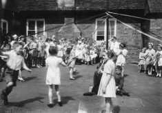 May Day children's maypole dance in village school yard