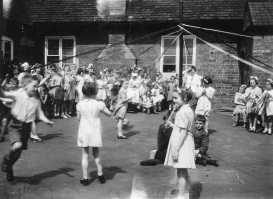 May Day children's maypole dance in village school yard