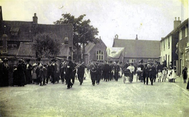 Village band marching in Church Street, inauguration of Edward Prince of Wales