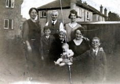 Family group to rear of house, probably in Bottesford