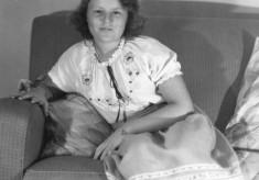 Helen Webb, sitting on a settee