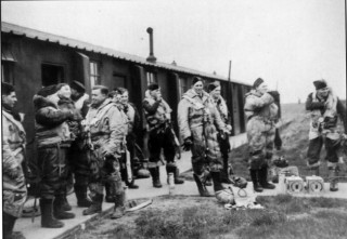 Aircrews gather outside the 'B' Flight office to await transport to take them to their aircraft, March 1943. Note the pigeons in their containers on the pathway, intended as an aid to air-sea rescue, and the varied flying gear