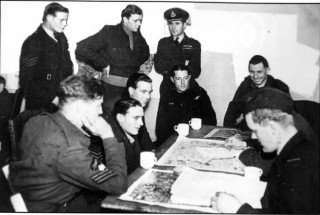 W/Cdr Comm talks to C/Capt Swain whilst the crew of P/0 C.5. Mant RAAF are given their post-raid debriefing by an Intelligence Officer. The Mant crew were shot down on the night of 11/12th March 1943 after attacking Stuttgart