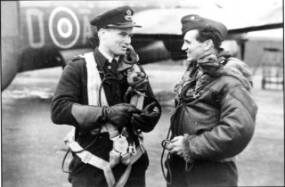 Twenty-four year old F/Lt Jack Sullivan (left) from Queensland talks to F/Sgt 'Freddie' Wilmot following their return from a raid, Spring 1943. Wilmot and his crew failed to return from Dusseldorf in June, whilst the Sullivan crew were lost whilst attacking Milan in August