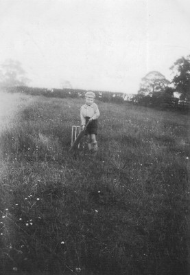 Gerald Coy, aged 5 playing cricket in Muston Church Field behind the church. 1936.