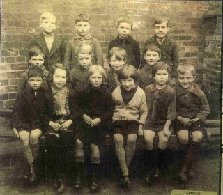 1928 Bottesford Primary School. Back Row (left to right): George Waudby; Stan Robinson; Derek Doubleday; Geoff Parr. Middle row: Philip Brewster; Frank Marston; Bernard Rippin; Bill Jackson. Front row: Jim Kirton; Kathleen Stanley (Mrs Mackley); Betty Parnham; Joyce Gamble; Pam Shirley; Derek Wing | Courtesy of Mr George Waudby