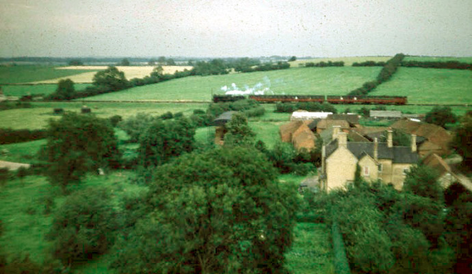 Looking north in 1956. This picture shows a steam-hauled passenger train traveling westwards bound for Nottingham, beyond the house and outbuildings of Beckingthorpe Farm, which was still very much an active farm owned by Mr Philip Marsh. | Michael Bradshaw
