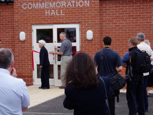 Mrs Lee cutting the opening ribbon assisted by Norman Robinson