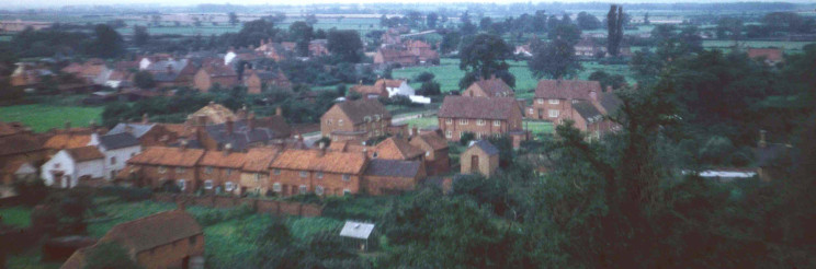 Looking towards the west end of the village, c.1956. This view is looking just south of west, towards the western part of Bottesford. To the left we can trace the houses of Chapel Street and Albert Street, with High Street in the distance. There are still open fields where the Walford Close and Spire View estates are today. The conspicuous terrace of cottages running into the centre of the view is the old Retford's Row, a close that stood behind Chapel Street from which it was reached via a covered archway that is still there. Behind Retford's Row stand the new houses of The Square, and behind them we can see the open field on the western side of Albert Street, at the rear of which runs Pinfold Lane. This view reminds us how much open space there used to be right in the middle of Bottesford.   Michael Bradshaw