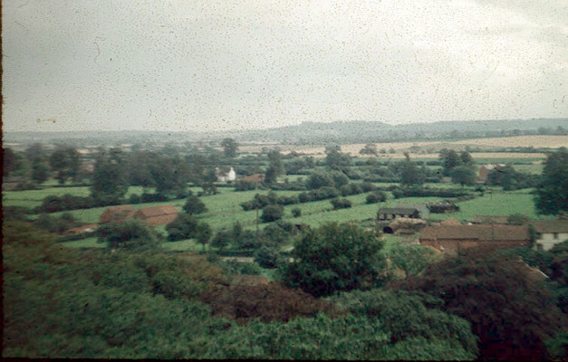 The vista southwards towards Belvoir Castle, c.1956. This picture looks approximately southwards, with Belvoir Castle tiny in the distance upon its hilltop belvedere. On the right are Daybell's Barn and Farmhouse, and the white building further away is a house on Manor Road, Easthorpe, but the scene is dominated by the serene expanse of open farmland that extends as far as the eye can see. | Michael Bradshaw