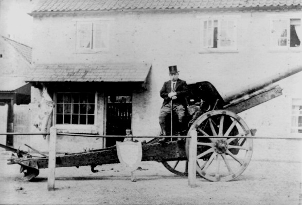 Arthur H. Taylor's father, Arthur E Taylor, seated on a captured German field gun outside his butcher's shop at the Cross, Bottesford.