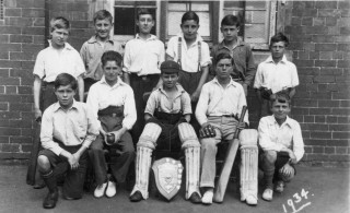 Bottesford School 1934 cricket team by the school building: the boys assembled for a group photograph in the school yard. | From the collection of Mrs Ada Bond