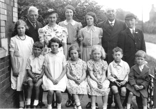 "The small Methodist Sunday School class stand together in the small forecourt of Muston's Methodist Chapel, now a private residence. The individuals in this superb picture were identified by Mrs Ruby Calcraft. Mrs Calcraft added that there were at this time three Calcraft families, who lived at (1) Sedgebrook Mill Farm (Sedgebrook parish), (2) Breeder Hills Farm (also in the adjoining parish of Sedgebrook, Lincolnshire), and (3) Sykes Lane Farm in Muston. Back row L ro R: Mary Calcraft (3) (born on 12th November 1929), Mr James North (Sunday School teacher, aged 80), Edna Calcraft (3), Marjorie Calcraft (2), Betty Calcraft (2), Mr Johnson (also a teacher, said to have been ""Lucy and Annie's father"" though it is unclear who this refers to for the present), Frank Calcraft (1). Front row L to R: Peter Robinson, Pat Calcraft (2), Hilda Calcraft (3), Ann Calcraft (3), Peter Calcraft (1), Melvyn Bradbury. 