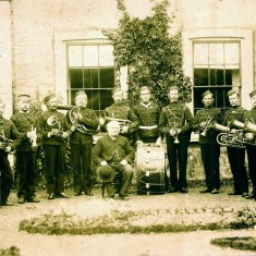 Bandsmen in uniform with Canon Norman outside Bottesford Rectory, c.1880. William Sutton is probably the cornet player next to the drummer.