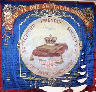 Bottesford Friendly Society banner showing damage to the fabric