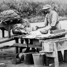Picture 2.On the moulding bench the brickmaker is taking clay from the heap on the bench