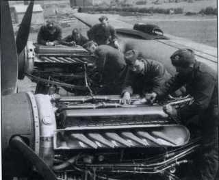 Engine fitters check over the two starboard Merlins of a 207 Squadron Lancaster on its Bottesford dispersal, summer 1942. In the distance are tents belonging to an A.T.C. summer camp.