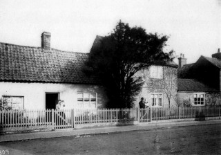 Norris family houses in the early 1900s - Nos 16 and 18 High St. Mr Ian Norris has assisted in identifying the people in this photograph. It shows Frank and Elizabeth Norris. They had twin sons Frank & John. Elizabeth is holding Frank and Frank is holding John. The single storey house to the left was built of mud. It was demolished in the 1960s and a new house was built - No 18. The brick built cottages to the right were converted into one dwelling - No 16