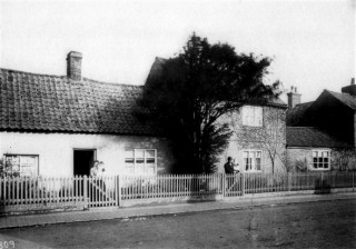 Norris family houses in the early 1900s - Nos 16 and 18 High St.  It shows Frank and Elizabeth Norris. They had twin sons Frank & John. Elizabeth is holding Frank and Frank is holding John