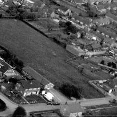 Aerial view of Parnham's Field in the mid 1980's showing the farm buildings to the right. The site of of Walford Close and the Woll Surgery