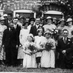 The Wedding of Horace Tinkler and Elsie Dunsmore, The Green, 1935. Kneeling front right: Connie and Arthur Guy. End of 2nd row, left: Mr. Skinner. End of 4th row, left: Thomas Waudby. Just visible at the very back in front of the window: Henry and Frank Dunsmore. Next to the Groom, left: Annie Dunsmore (nee Ricketts). Back row, visible between the Groom and Bride: Louisa Ann Dunsmore (nee Bellamy). Back row, third from right, in white hat: Betty Whatton (nee Waudby). Between the two bridesmaids, centre: Margaret Waudby, aged 8. We can add, thanks to Jean Rigby, that the gentleman second from left in the third row is Martin Killeen, and the lady to his left, wearing a hat with a diagonal ribbon, is his wife Mabel (nee Tinkler).