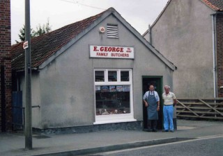 Eric George with Ian Norris in the early 1990s. Modern hygiene regulations required the removal of the original stable door, renovation of the windows and installation of refrigeration and ventilation. The hipped  roof shown in the early photograph has been replaced with a louvered vent