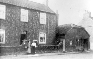 William Miller's farm and shop to the right in the early 1900s