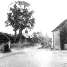 Grantham Road from The Red Lion c. 1900. The building on the left is the forge. Beyond that the School Master's House can be seen. On the right is Daybell's barn.