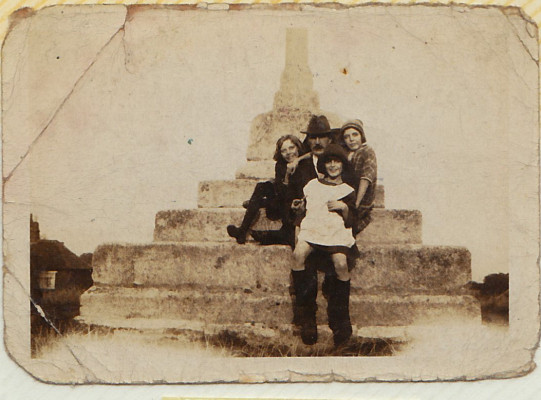 Iris, Irene and Phyllis Sharpe on the village cross with Mr Challands circa 1924