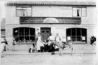 J.D. Robinson (far left - b.1864, d.1947) moved his butchery and pork pie business from Queen Street to Market Street in 1899 although the 1899 Wright's Directory, presumably compiled in 1898, still lists him in Queen Street. The 1901 Census shows J.D. Robinson as working as a butcher at 15 Market Street and Joseph Martin as a baker and confectioner at 13 Market Street. We can also identify the children in the photograph from the 1901 census information. From left to right - the children are: James, W. (b.1893, d.1934); Annie (b.1891); Victoria, M (b.1897) - on the knee of Mrs Caroline Robinson (b. 1856, d.); George (b.1889, d.1941) - holding the donkey; Richard (b. 1895, d.1918 'in the Great War')  - sitting on the donkey.  By 1908 Kelly's Directory gives G.H. Goodson as a butcher on Market Street. The 1928 Kelly's Directory then lists Harry Bugg a butcher at these premises (as shown in one of the previous photographs). After WW2 Mr Frank and Mrs Maisie Goodson ran their butcher and pork pie business from these premises. Their son Andrew Goodson converted it to a restaurant in the early 1990's. It is now Paul's Restaurant. The former slaughter house is now the 'Wine Lounge'.
