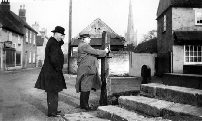Mr Terry (left) and friend examining Bottesford stocks in 1921.