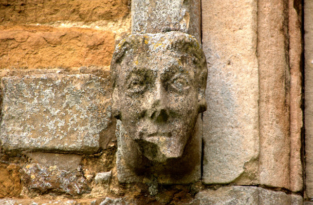 Label-end carving, Muston. Head of a man.