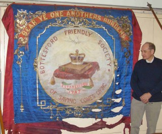 Mike Saunders unveils the Bottesford Friendly Society's marching banner | Bottesford Local History Society