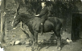 Tom Samuel on a pony by the barns at the back of the Market Street Store
