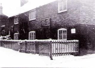 Winter scene showing the sign over the front door
