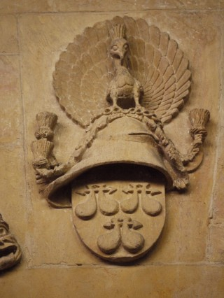 Above the eastern pillar of the N arcade of the nave: shield bearing the arms of the de Roos, beneath the Cap of Maintenance and the peacock resplendant.