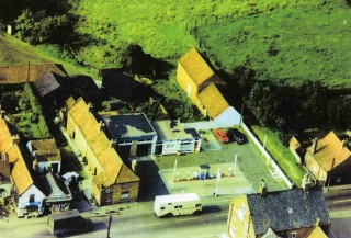 1960s aerial view showing Standley's Cottages and the recently built garage forecourt on the site of Hart's and of Ottley's shops. The cottages were demolished to create access from the High Street to the barns to the rear of the garage. These barns were then converted into a dwelling in the  1980s.